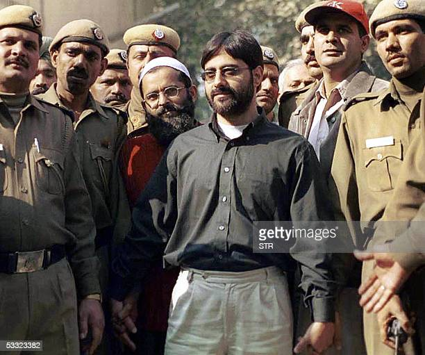 In this picture taken 18 December 2002 Indian police present Mohammed Afzal SAR Geelani and Shaukat Hussain to media representatives as they arrive...