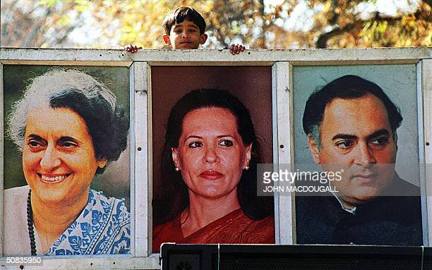 In this picture taken 19 January 1998 A young Indian boy peers out from the top of a Congress Party campaign truck featuring an enlarged photograph...