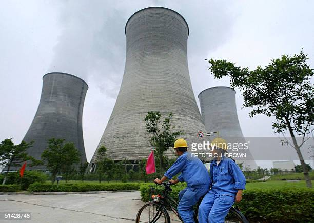 In this picture taken 21 August 2004 workers of a power plant cycle past power stations in Guangan in southwest China's Sichuan Province French...