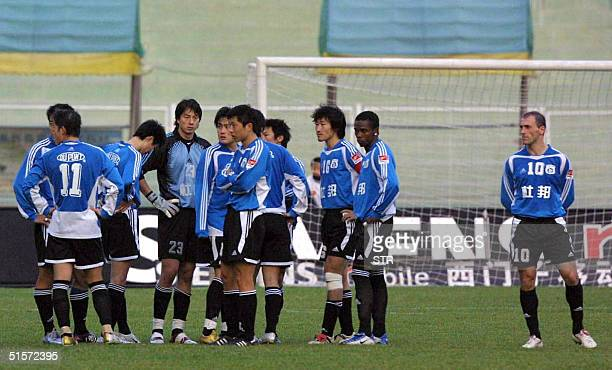 In this picture taken 24 October 2004 Dalian Shide players gather before storming off the pitch after an alleged referee blunder in Dalian during...