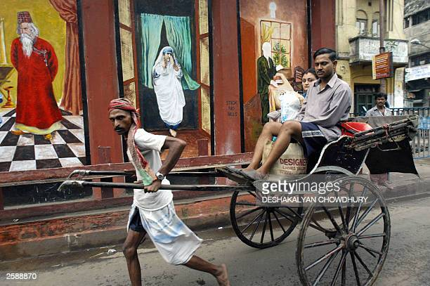 In this picture taken 24 September 2003 a Calcutta rickshaw puller takes his passengers past a wall painting showing portraits of Mother Teresa and...