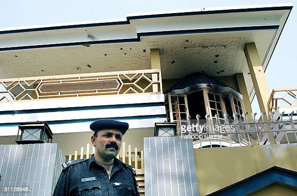 In this picture taken 25 July 2004 a Pakistani policeman stands guard infront of the house where security personnel fought a gun battle with a group...