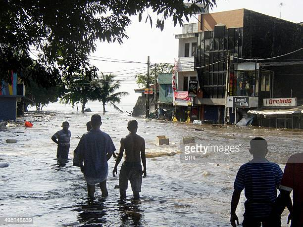 In this picture taken 26 December 2004 Sri Lankan pedestrians walk through floodwaters in a main street of Galle after the coastal town was hit by a...