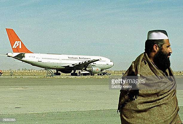In this picture taken 28 December 1999 an Afghan man walks on the runway as an aircraft of Indian Airlines hijacked by Islamic Kahsmiri militants...