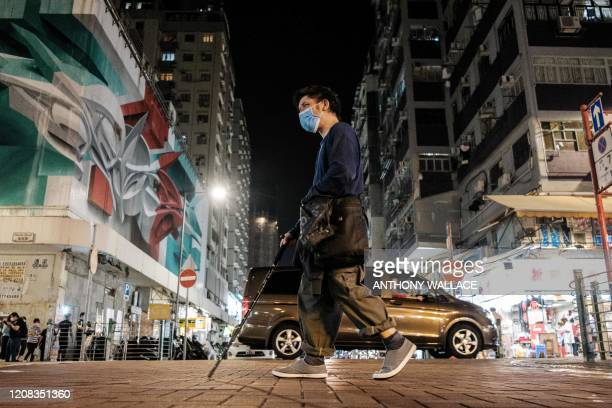 In this picture taken at night on March 26 Leung Pingkuen who is virtually blind and usually sleeps in a 24hour McDonalds uses a hiking stick as a...