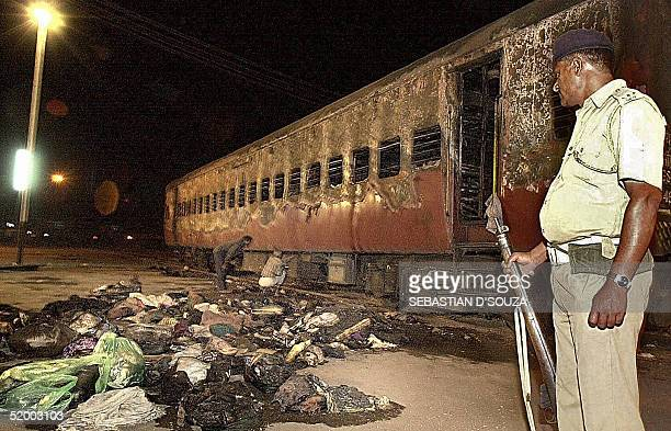In this picture taken early 28 February 2002, an Indian policeman looks towards a burnt train coach and belongings of Hindu activists at Godhra...