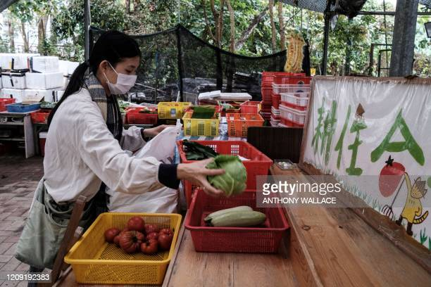 In this picture taken in Hong Kong on March 18 Mandy Tang, who used to be an interior designer and is now a housewife, bags up her vegetables at Ma...