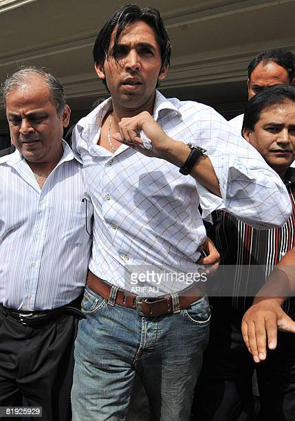 In this picture taken in June 20 Pakistani cricketer Mohammad Asif walks with others as he leaves the arrivals hall at Allama Iqbal International...