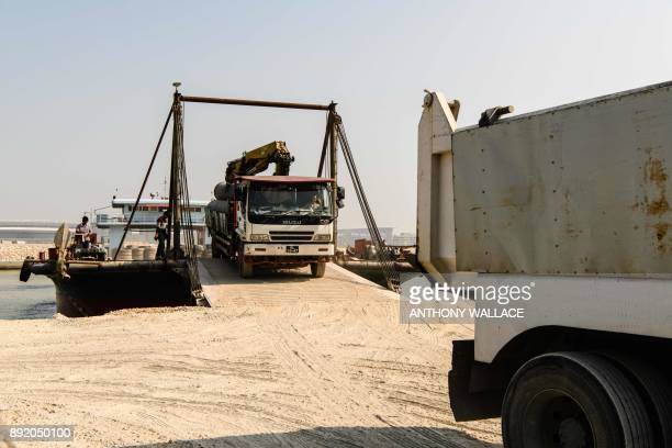 In this picture taken in Macau on December 6 a construction vehicle is driven off a ferry after it was transported from an artificial island which...
