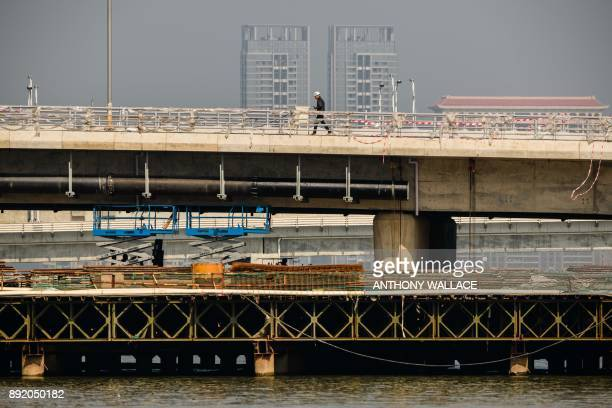 In this picture taken in Macau on December 6 a labourer walks on a section of the Hong KongZhuhaiMacau Bridge in front of a view of buildings in...