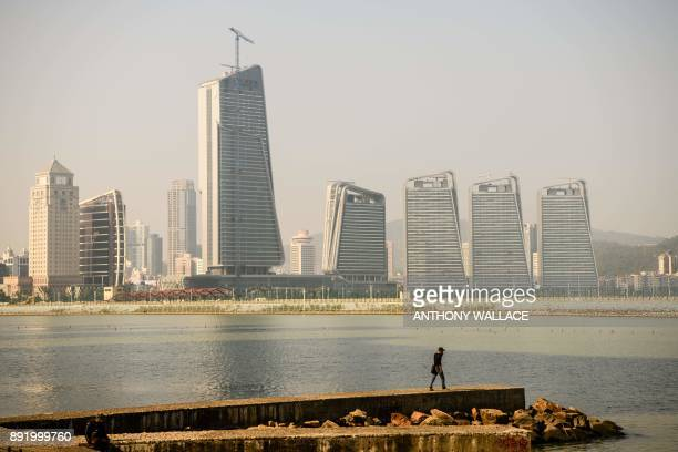 In this picture taken in Macau on December 6 a man looks towards the Zhuhai border and a road that leads to an artificial island which was built for...