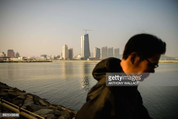 In this picture taken in Macau on December 6 a man walks in front of a view of the Zhuhai border and a road that leads to an artificial island which...