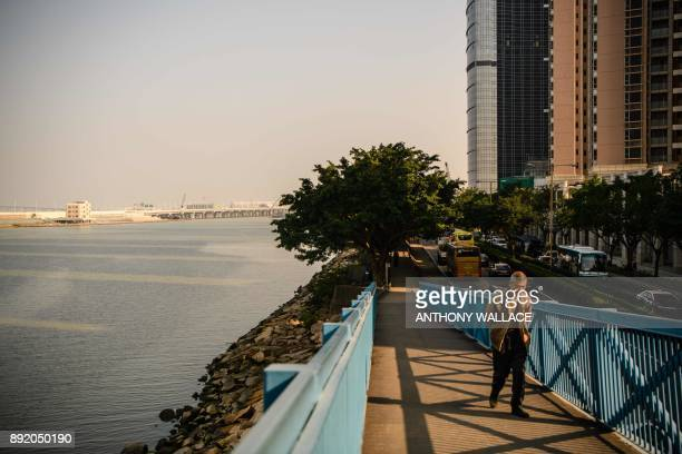 In this picture taken in Macau on December 6 a man walks on an overpass near an artificial island which was built for the Hong KongZhuhaiMacau Bridge...