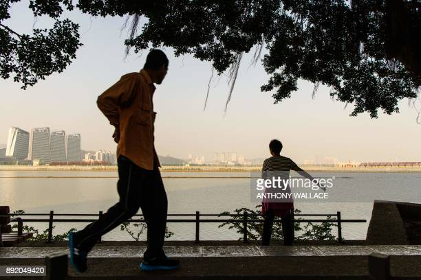 In this picture taken in Macau on December 6 a woman exercises as she faces a view of the Zhuhai border and a road that leads to an artificial island...