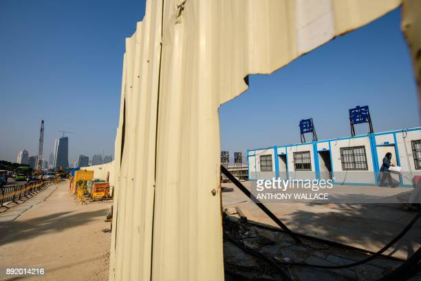 In this picture taken in Macau on December 6 a woman walks within a construction site of the Hong KongZhuhaiMacau Bridge as buildings in Zhuhai are...