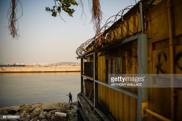 In this picture taken in Macau on December 6 an angler fishes below a construction site entry point for an artificial island which was built for the...