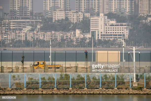 In this picture taken in Macau on December 6 labourers fix barbed wire on top of a fence at the Zhuhai border in front of a road that leads to an...
