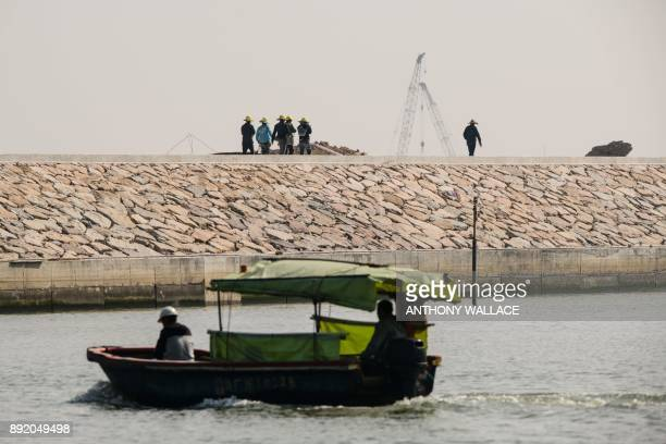 In this picture taken in Macau on December 6 labourers walk away from a small boat that ferried them to an artificial island which was built for the...