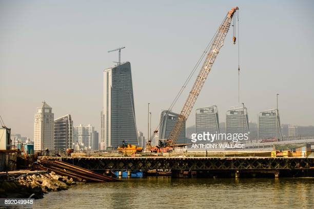In this picture taken in Macau on December 6 labourers work on a road that leads to an artificial island which was built for the Hong KongZhuhaiMacau...