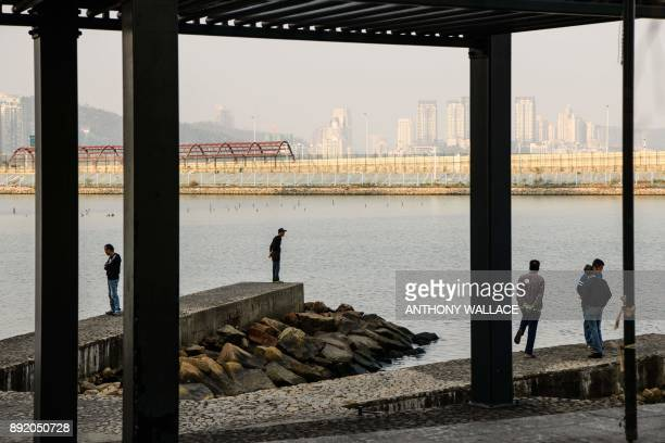 In this picture taken in Macau on December 6 people look towards the Zhuhai border fence and a road that leads to an artifical island which was built...