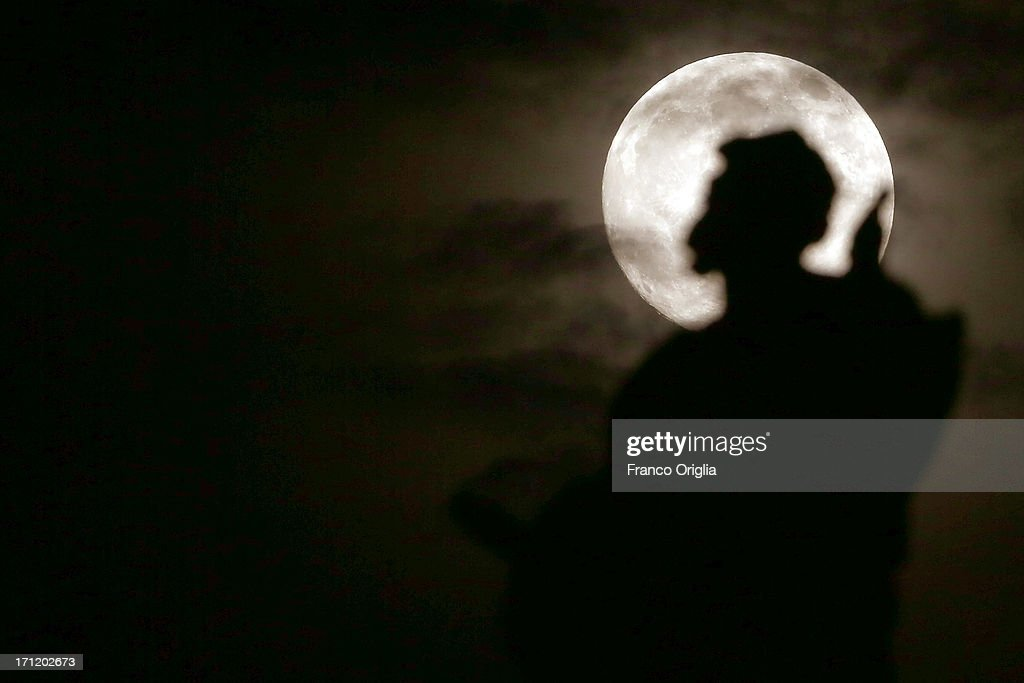 In this picture taken in the night between June 22 and June 23 the moon with a silhouette of the sculpture of the Colonnade overlooking St. Peter's Square on June 23, 2013 in Rome, Italy. Tonight a pink full moon is expected to appear in the sky of Rome. The event occurs once a year when the moon reaches its nearest point to Earth, making it appear much larger than usual as well as being a peculiar shade of pink. The spectacle can be seen throughout the world, weather permitting.