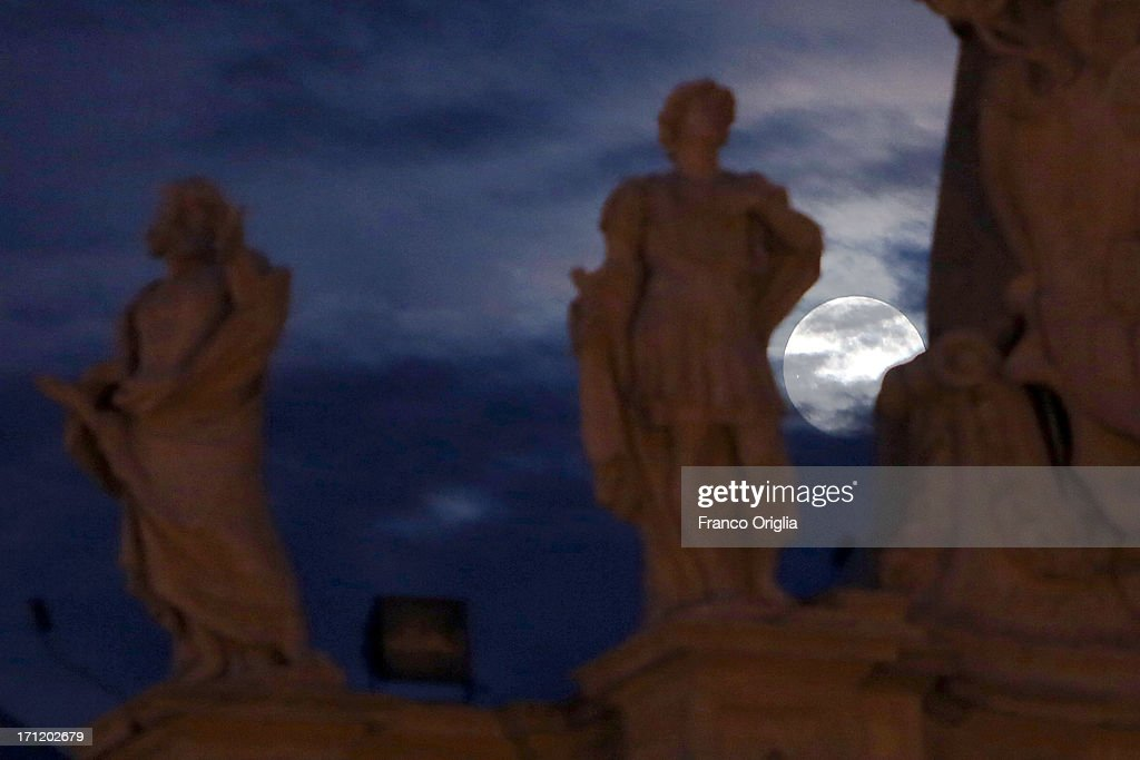 In this picture taken in the night between June 22 and June 23 the moon is framed by a sculpture of the Colonnade overlooking St. Peter's Square on June 23, 2013 in Rome, Italy. Tonight a pink full moon is expected to appear in the sky of Rome. The event occurs once a year when the moon reaches its nearest point to Earth, making it appear much larger than usual as well as being a peculiar shade of pink. The spectacle can be seen throughout the world, weather permitting.