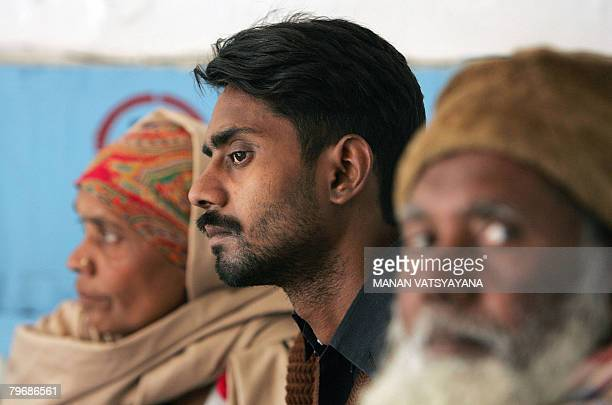 In this picture taken January 29 Indian labourer Shakeel Ahmed rests on a hospital bed with his parents in Gurgaon some 30 kms south of New Delhi...