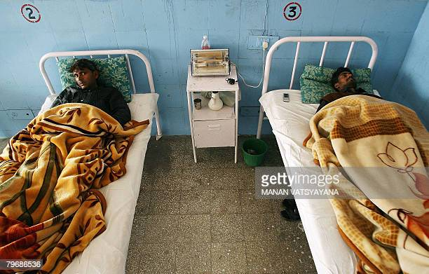 In this picture taken January 29 Indian labourers Mohammad Salim and Shakeel Ahmed rest on hospital beds in Gurgaon some 30 kms south of New Delhi...