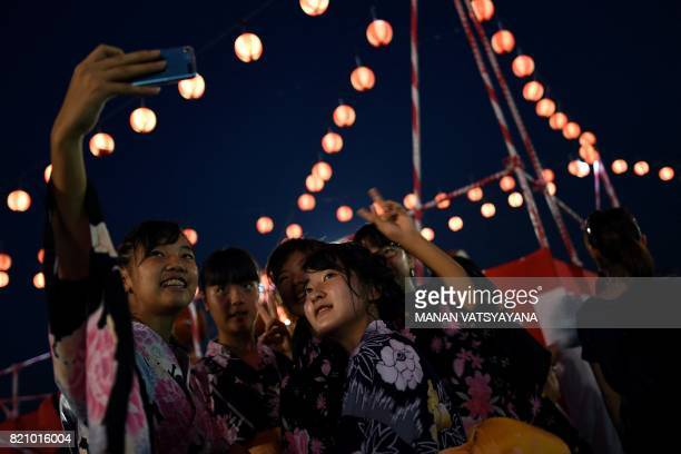 TOPSHOT In this picture taken July 22 2017 Japanese girls living in Malaysia wearing traditional kimono costume pose for a selfie during the annual...