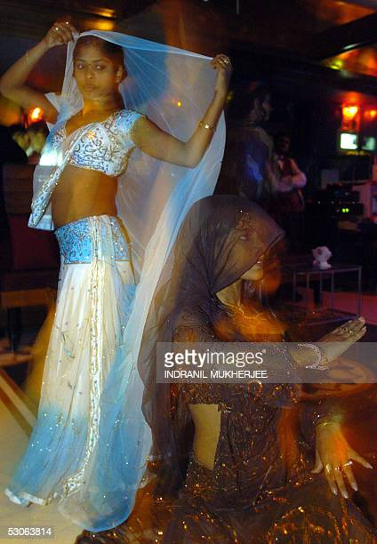 In this picture taken late 06 May 2005 Indian men watch as dancer Nikita and Rani perform a routine at a dancebar in Mumbai The western Indian state...