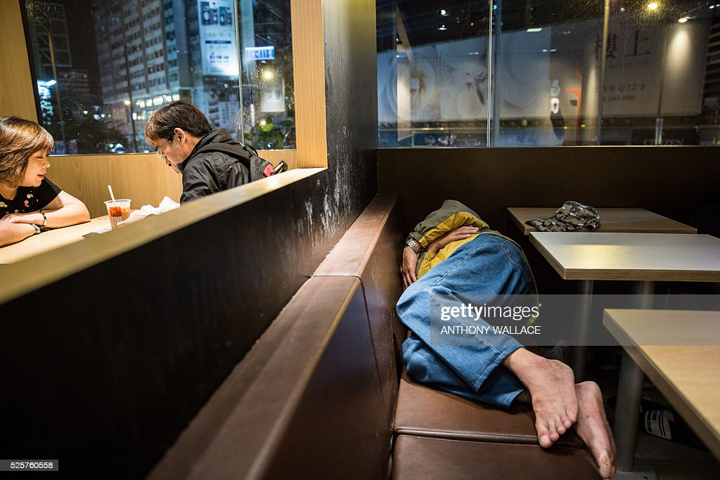 In this picture taken late on April 8, 2016, a couple (L) sit down for a meal as a man sleeps on a seat at a McDonalds outlet in the Kowloon district of Hong Kong. / AFP / Anthony WALLACE / To go with 'HongKong-social-politics-homeless' FEATURE by Laura Mannering