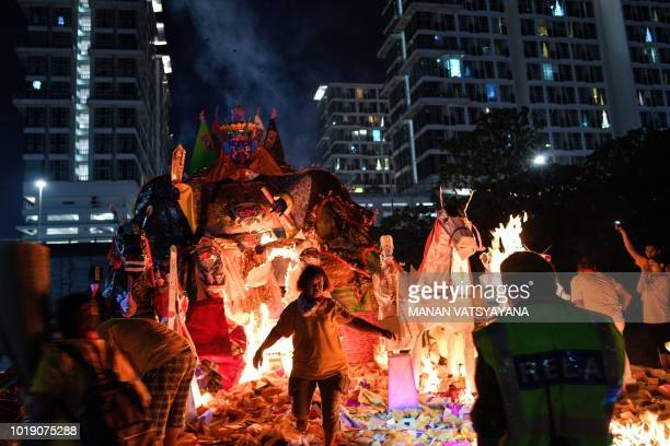 In this picture taken late on August 18 an ethnic MalaysianChinese devotee runs back after setting a paper statue of Chinese deity Da Shi Ye or the...