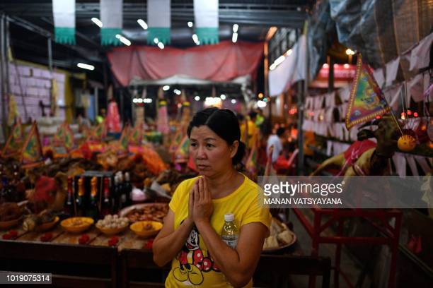 """In this picture taken late on August 18 an ethnic Malaysian-Chinese devotee offers prayers in front of a paper statue of Chinese deity """"Da Shi Ye"""" or..."""