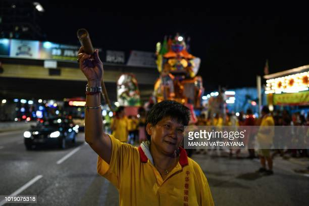 In this picture taken late on August 18 ethnic MalaysianChinese devotees carry a paper statue of Chinese deity Da Shi Ye or the Guardian God of...