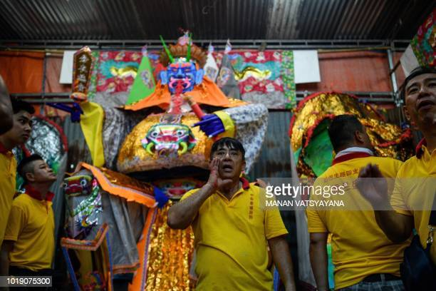 """In this picture taken late on August 18 ethnic Malaysian-Chinese devotees stand in front of a paper statue of Chinese deity """"Da Shi Ye"""" or the..."""