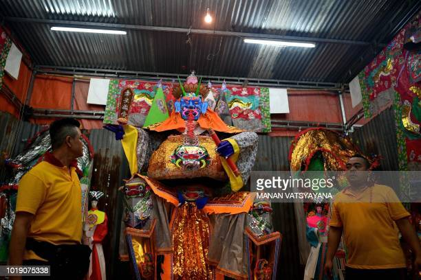 "In this picture taken late on August 18 ethnic Malaysian-Chinese devotees stand in front of a paper statue of Chinese deity ""Da Shi Ye"" or the..."
