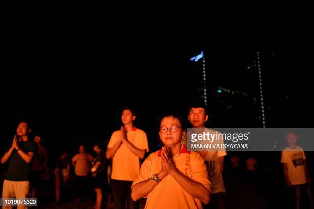 "In this picture taken late on August 18 ethnic Malaysian-Chinese devotees offer prayers after burning a paper statue of Chinese deity ""Da Shi Ye"" or..."