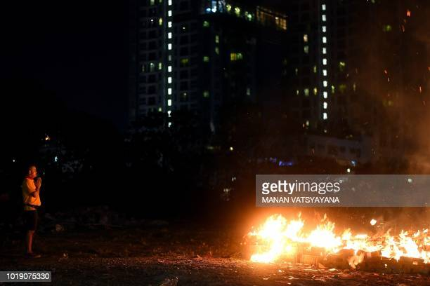 """In this picture taken late on August 18 ethnic Malaysian-Chinese devotees offer prayers after burning a paper statue of Chinese deity """"Da Shi Ye"""" or..."""