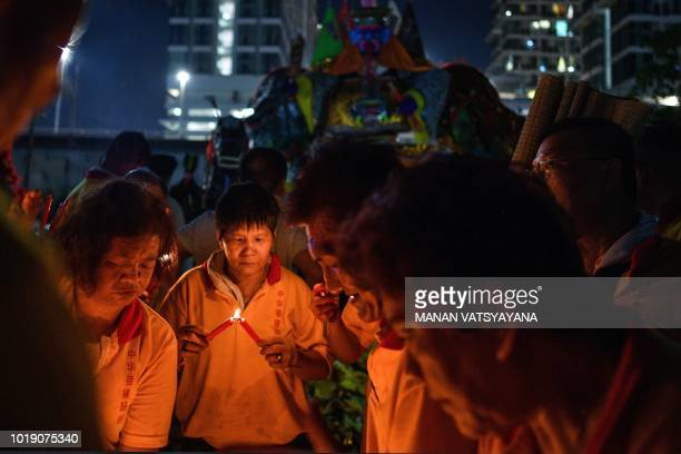 "In this picture taken late on August 18 ethnic Malaysian-Chinese devotees prepare to burn a paper statue of Chinese deity ""Da Shi Ye"" or the Guardian..."