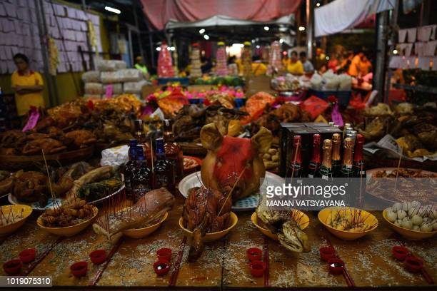 In this picture taken late on August 18 food sits on a table as an offering in front of a paper statue of Chinese deity Da Shi Ye or the Guardian God...