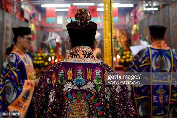 In this picture taken late on August 18 monks offer prayers in front of a paper statue of Chinese deity Da Shi Ye or the Guardian God of Ghosts to...