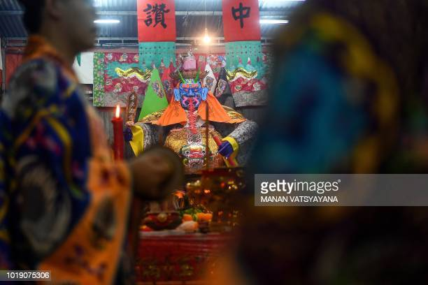 """In this picture taken late on August 18 monks offer prayers in front of a paper statue of Chinese deity """"Da Shi Ye"""" or the Guardian God of Ghosts, to..."""