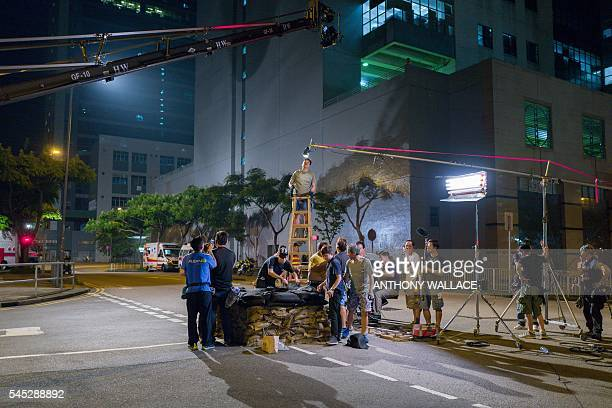 In this picture taken late on May 23 members of a film crew working with local director Herman Yau prepare to film a scene for their movie Shock Wave...