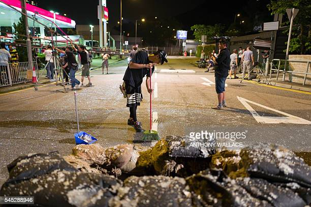 In this picture taken late on May 23 members of a film crew working with local director Herman Yau clean up following a controlled explosion on the...