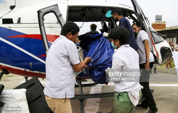 In this picture taken on 23 May Nepali officials unload bodies of Everest climbers who died in previous seasons at the helipad of Teaching Hospital...