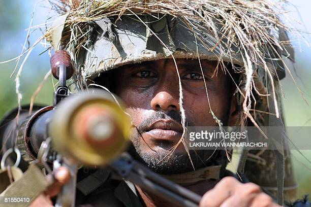 In this picture taken on April 06 a Sri Lankan Army soldier patrols along the 'de facto' frontline at Muhamalai in the Jaffna Peninsula some 400 km...
