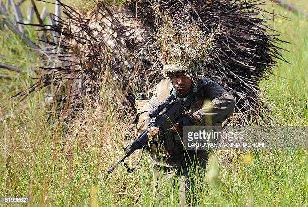In this picture taken on April 06 Sri Lankan Army soldiers patrol along the 'de facto' frontline at Muhamalai in the Jaffna Peninsula some 400 km...