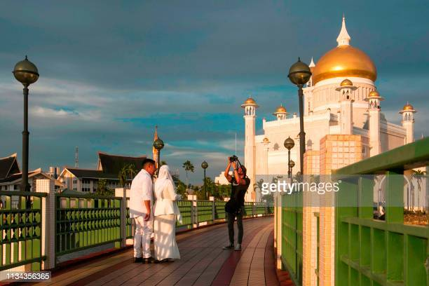 TOPSHOT In this picture taken on April 1 2019 a newlywed couple has their photographs taken at the Sultan Omar Ali Saifuddien mosque in Bandar Seri...