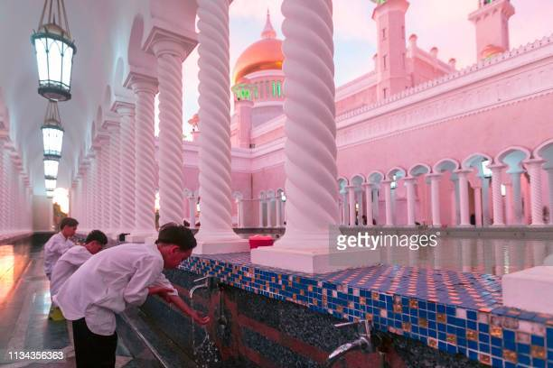 In this picture taken on April 1 2019 children perform ablution before praying at the Sultan Omar Ali Saifuddien mosque in Bandar Seri Begawan The...