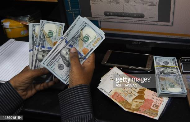 In this picture taken on April 15 a Pakistani dealer counts US dollars at a currency exchange shop in Karachi